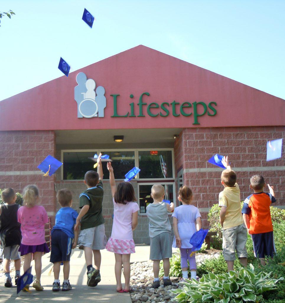 Children throwing graduation hats